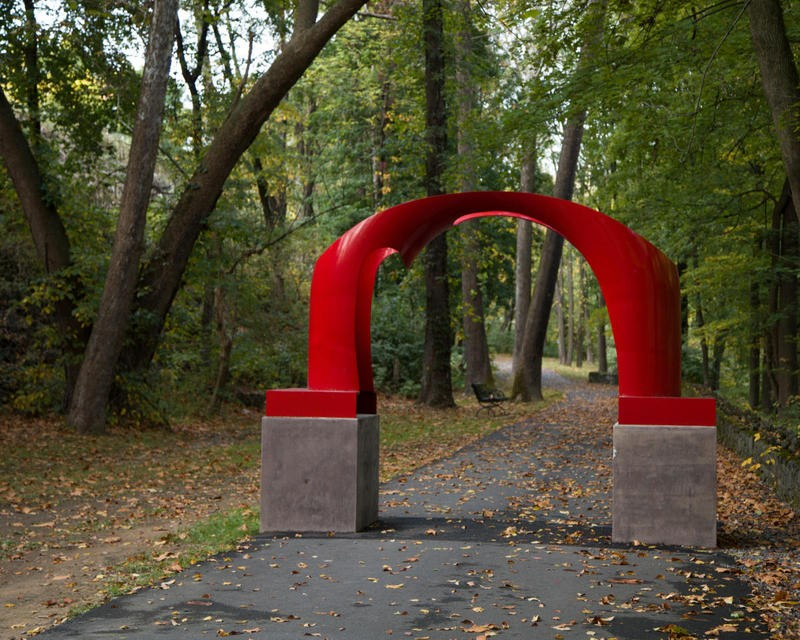 red sculpture arch on walking path through wooden area