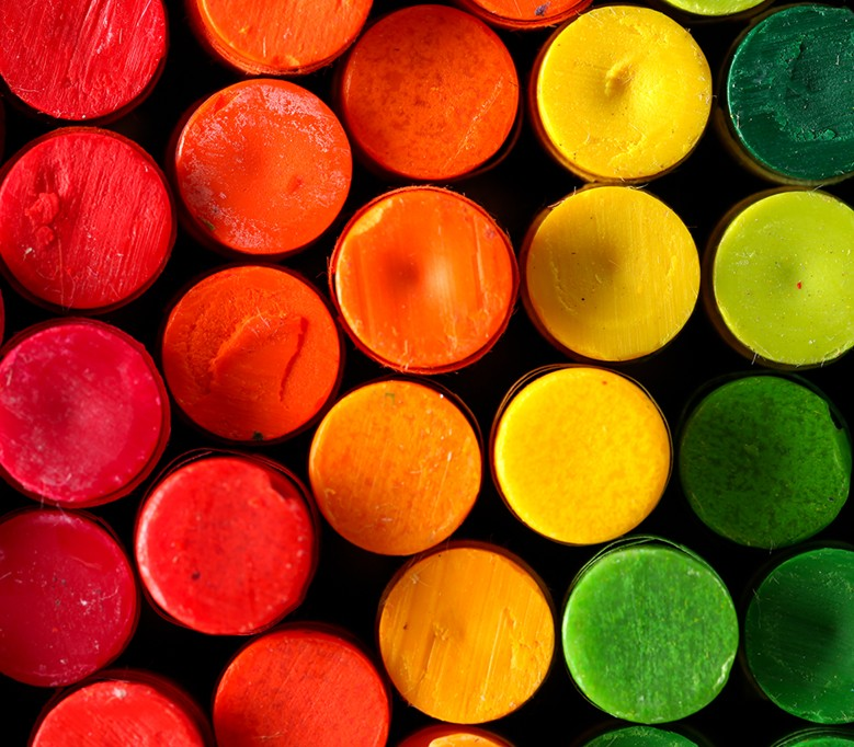 top down closeup view of crayons as circles in rainbow spectrum