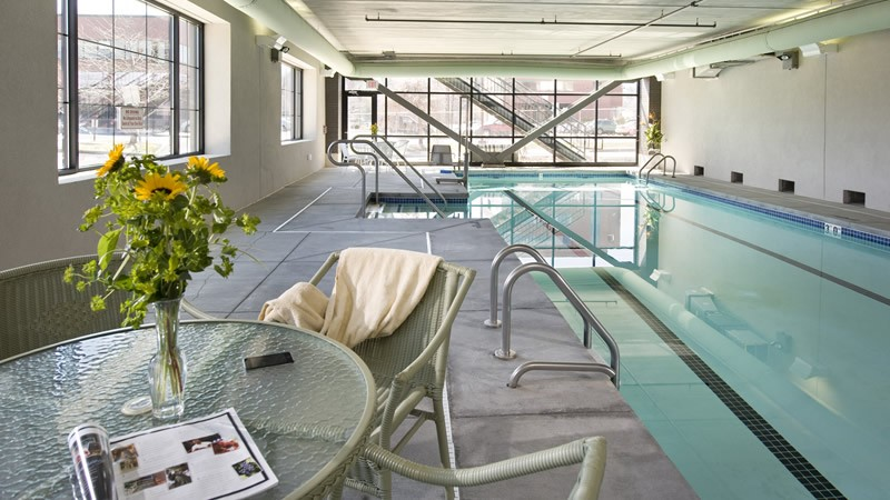 indoor pool with tables and lounge chairs
